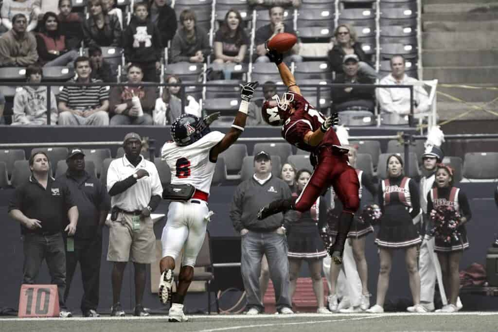 A wide receiver in a maroon jersey makes a one handed catch.