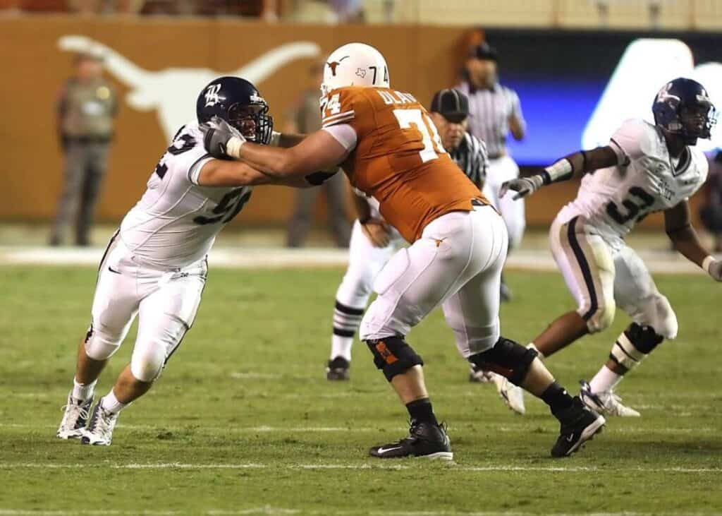 The offensive tackle on the Texas Longhorns looks to impede the Rice player.