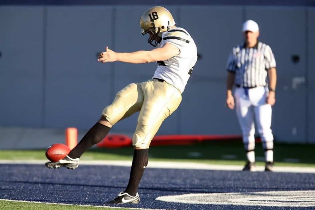 College football punter punts the ball away.