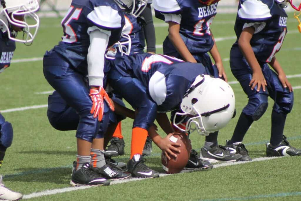 A youth football center gets ready to hike the ball.