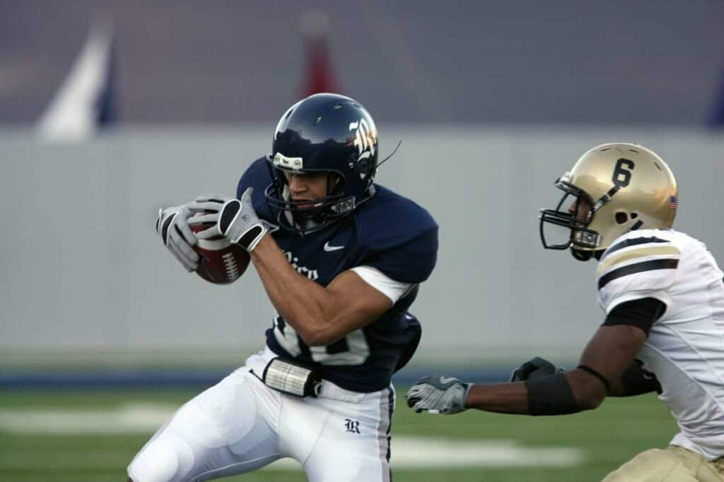 A Rice running back looks to gain some yards by running up the sideline.
