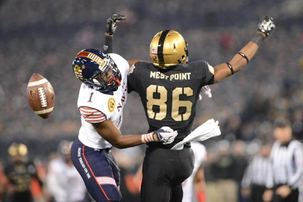 A Navy football player disrupts a West Point player from catching the ball.