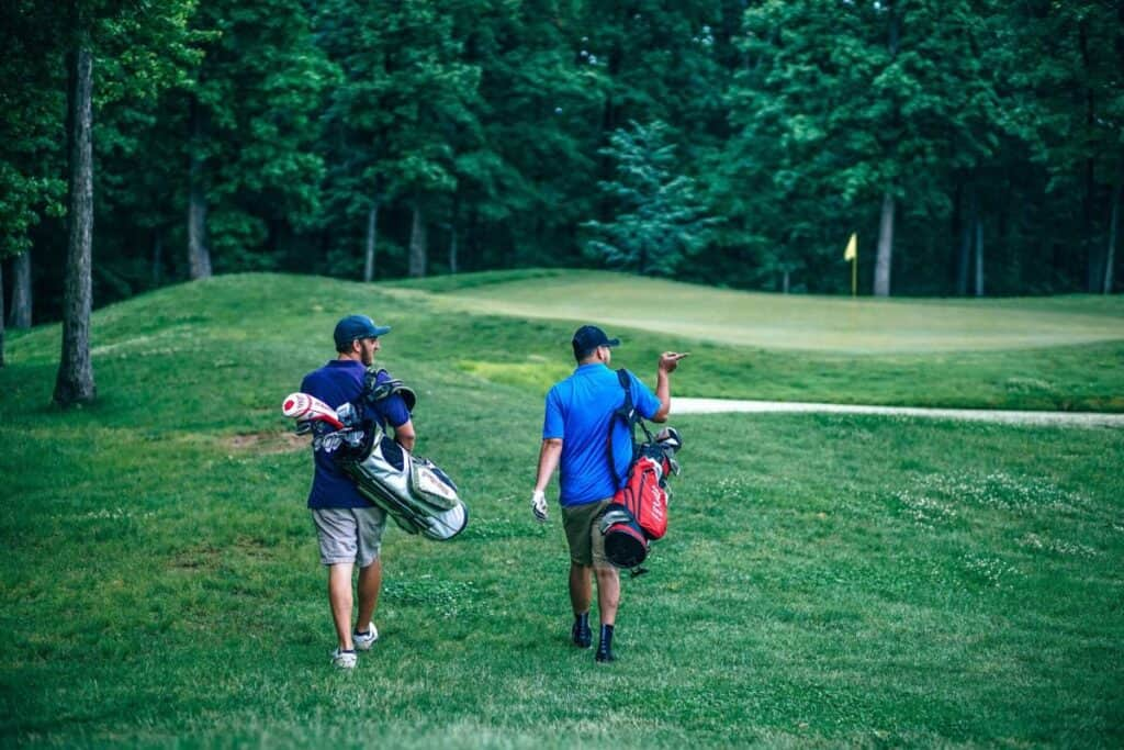 Two golfers walk toward the green to putt their balls.