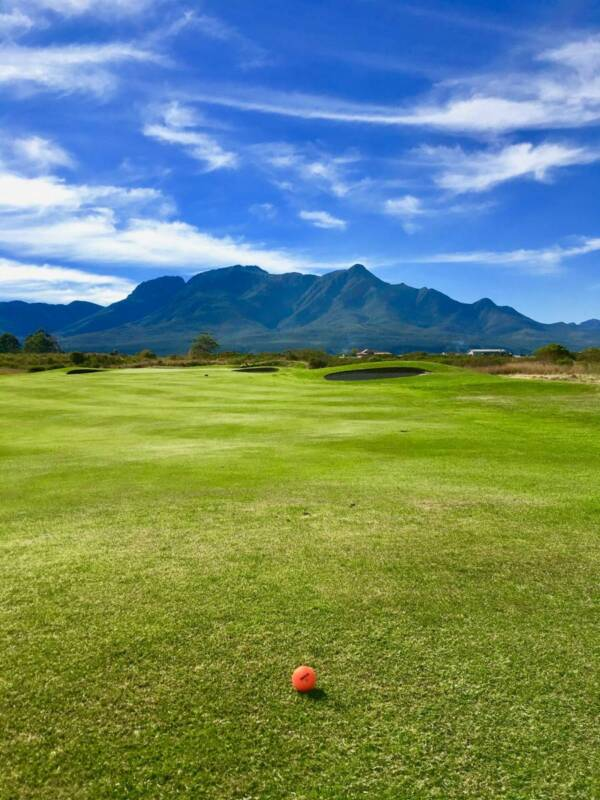 An orange golf ball sits on the fairway with mountains in the background.