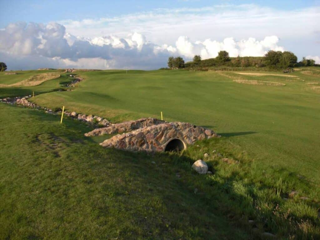 A small bridge connects two holes on a golf course.