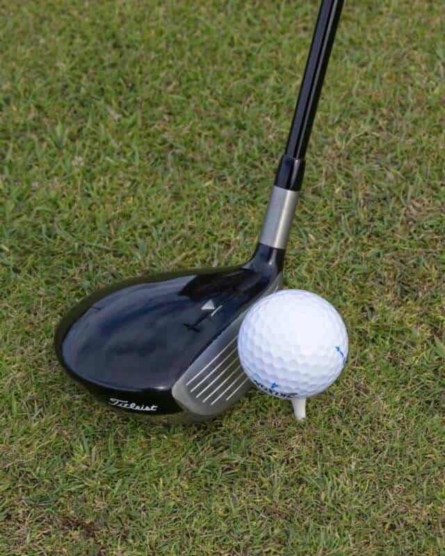A Titleist driver next to a golf ball on a tee.