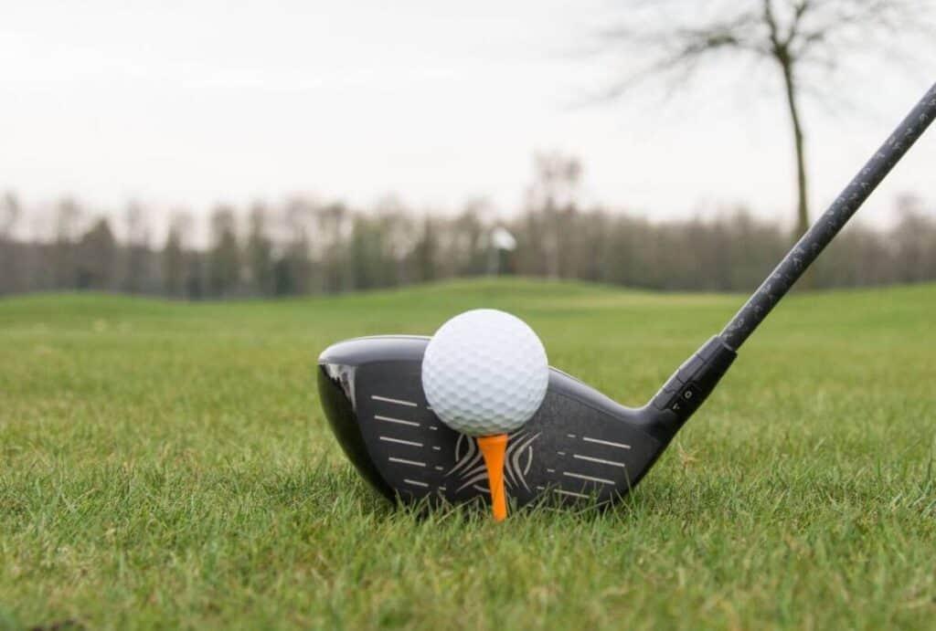 A golfer lines up their driver behind a tee'd up ball.