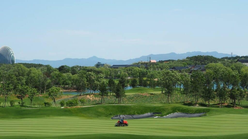 A groundskeeper mowing the fairway on a golf course.