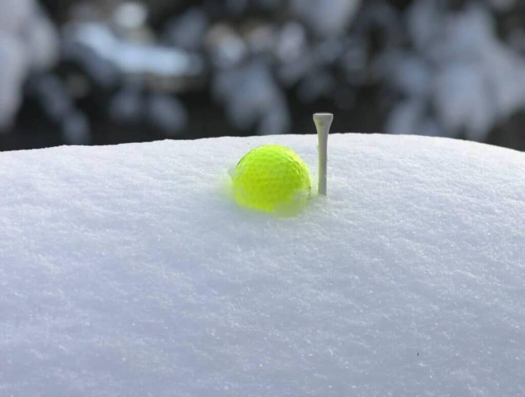 Golf ball and tee sitting in the snow.