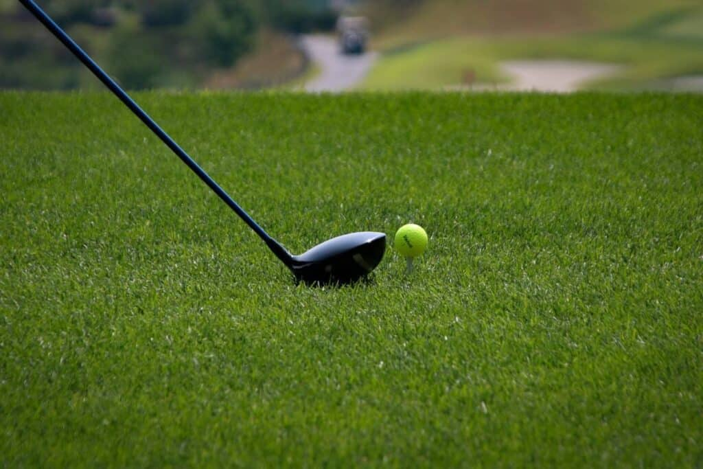 A golfer about to hit a yellow golf ball with their driver.