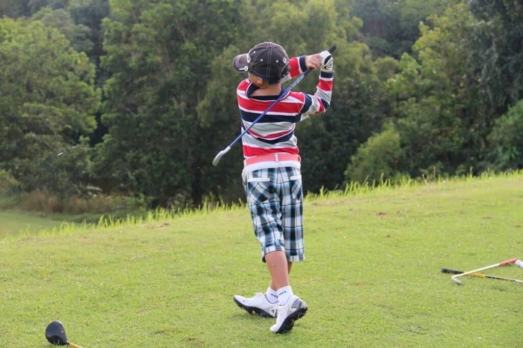 A junior golfer slices the golf ball.