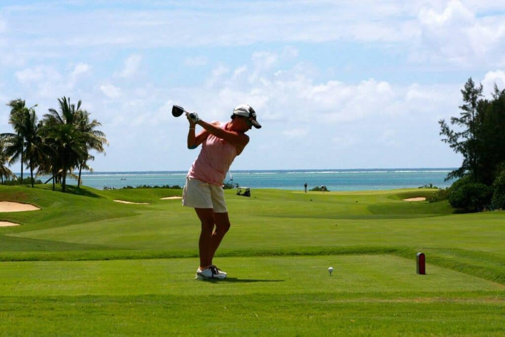 Female golfer about to tee off on a hole.
