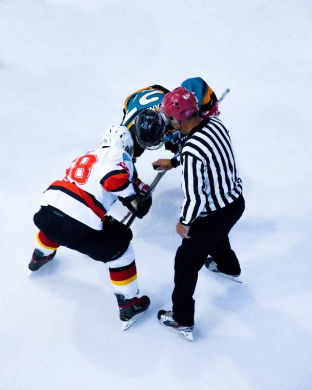 Two professional hockey players line up for a faceoff.