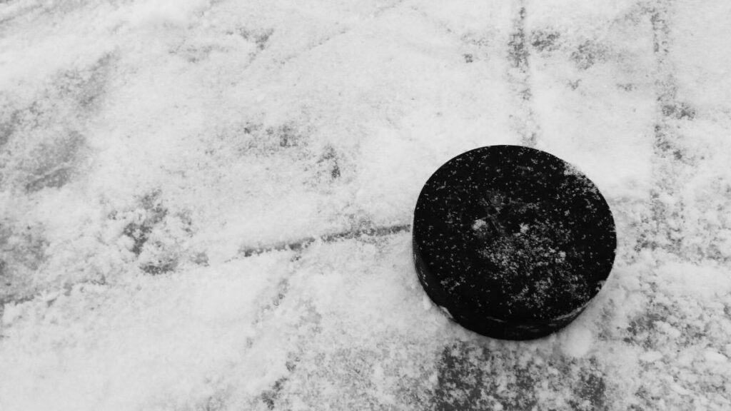 A hockey puck sits on a sheet of ice.