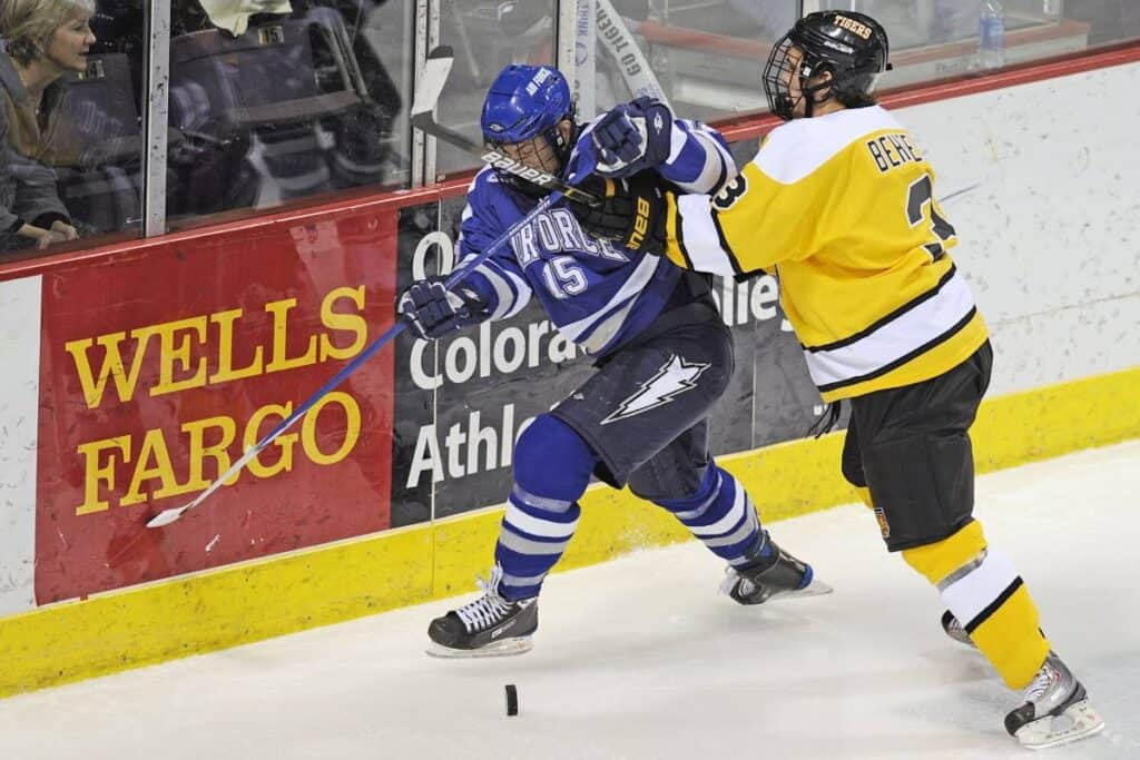 A college hockey player in yellow checks a player in blue.
