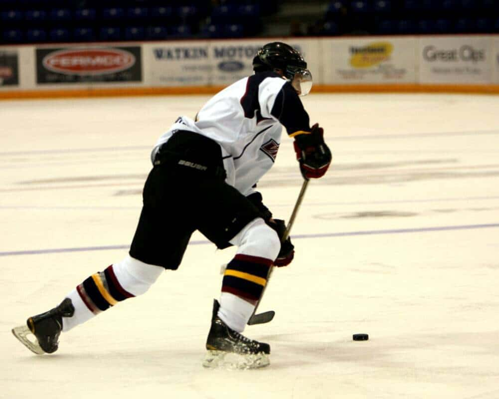 A hockey player sets up for a slapshot near the blue line.