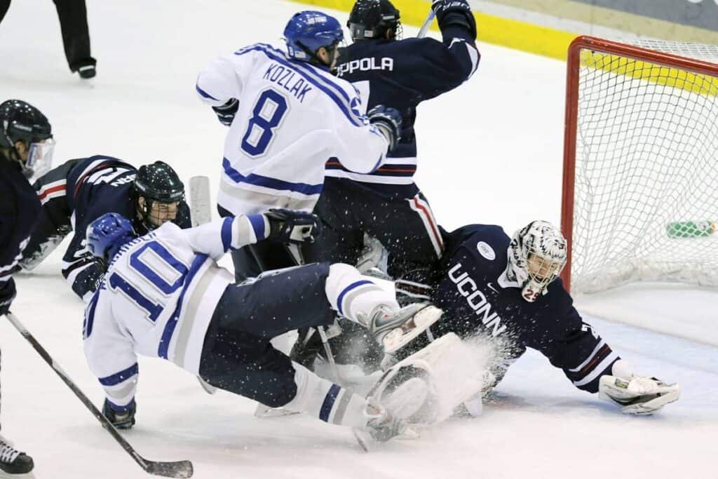 College hockey players battle near the net for the puck.