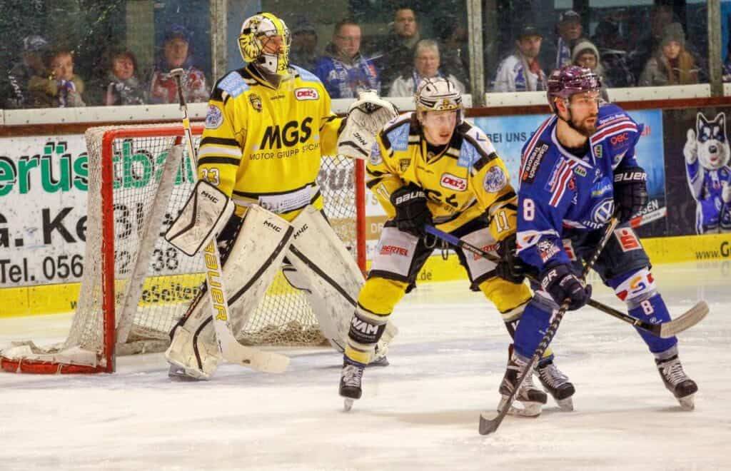 Two hockey players battle for position in front of the net.
