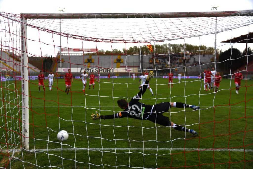 A soccer player shoots the ball past a diving goalkeeper on a penalty kick.