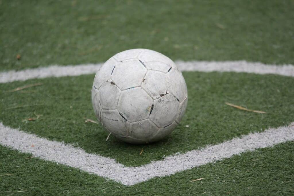 A white soccer ball gets prepared for a corner kick.