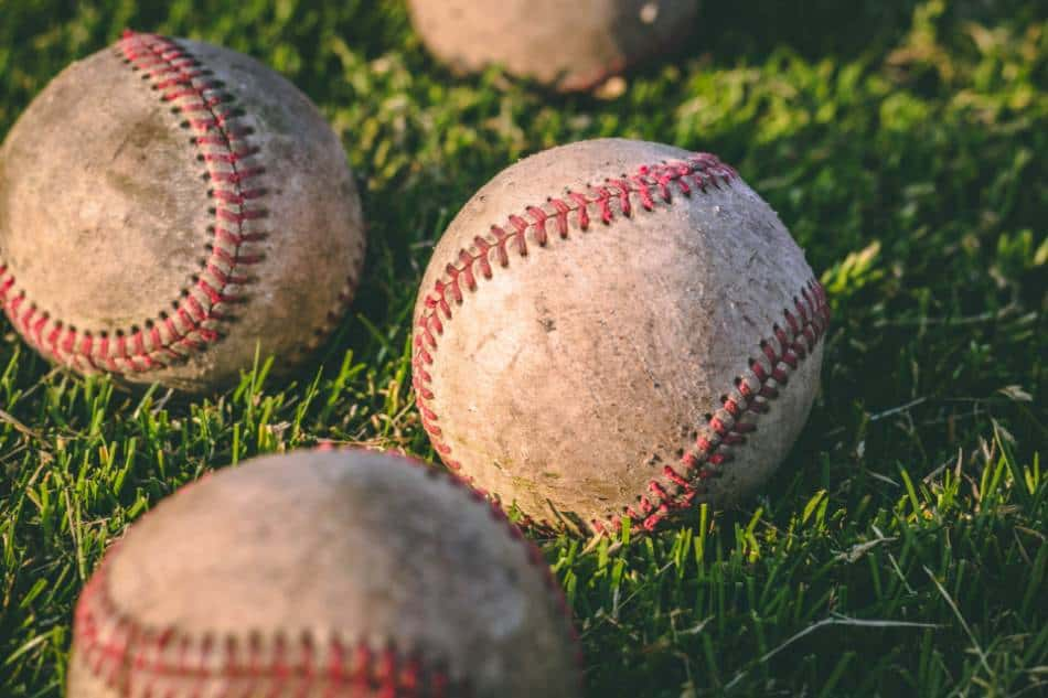 Baseballs sitting on the grass.