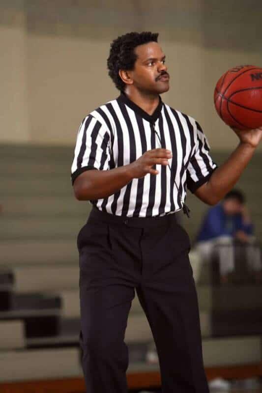 A basketball referee holds a ball.