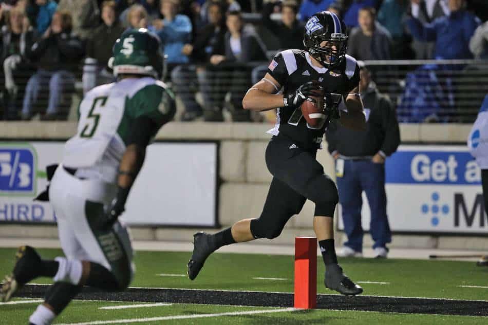 A college football player scores a touchdown.