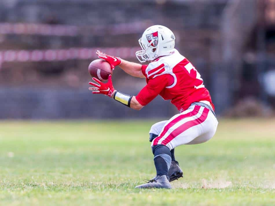 A college football player catches the ball.