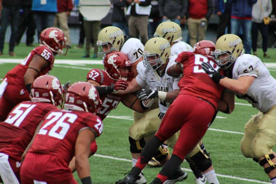 Both college football teams clash at the line of scrimmage.