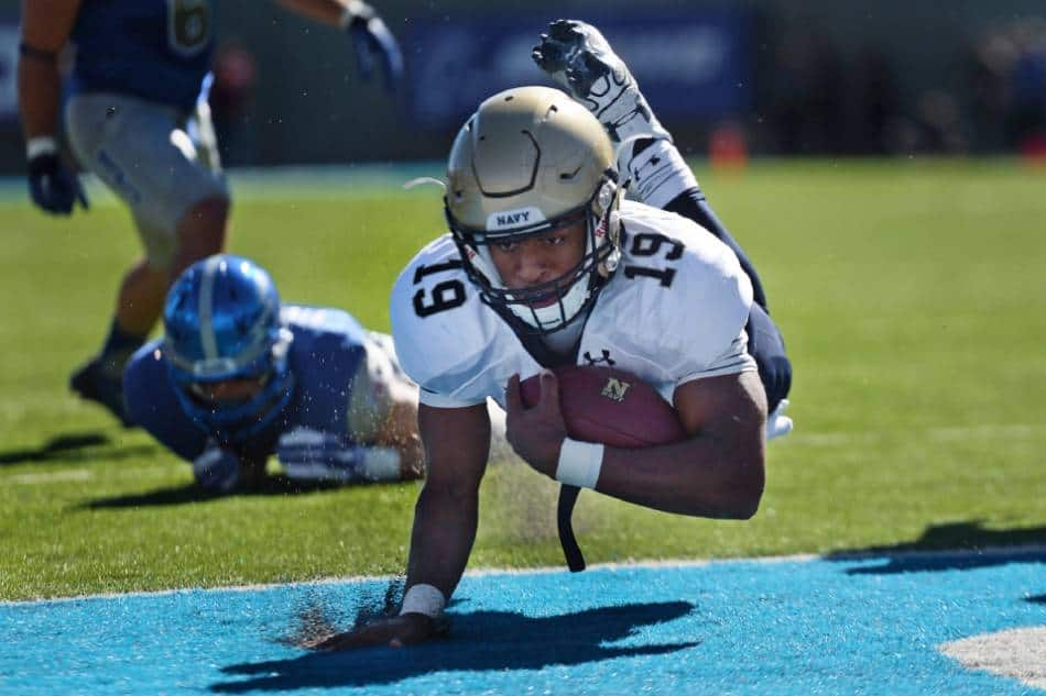 A college football player dives into the end zone.