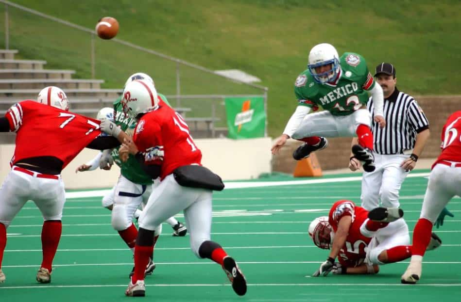 Quarterback in red throws the football.