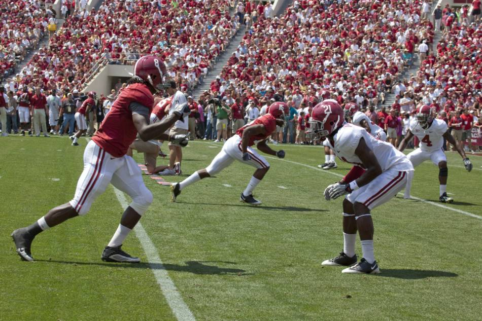 College football wide receivers line up out wide.