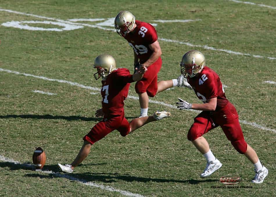 A kicker in red and gold kicks an onside kick.