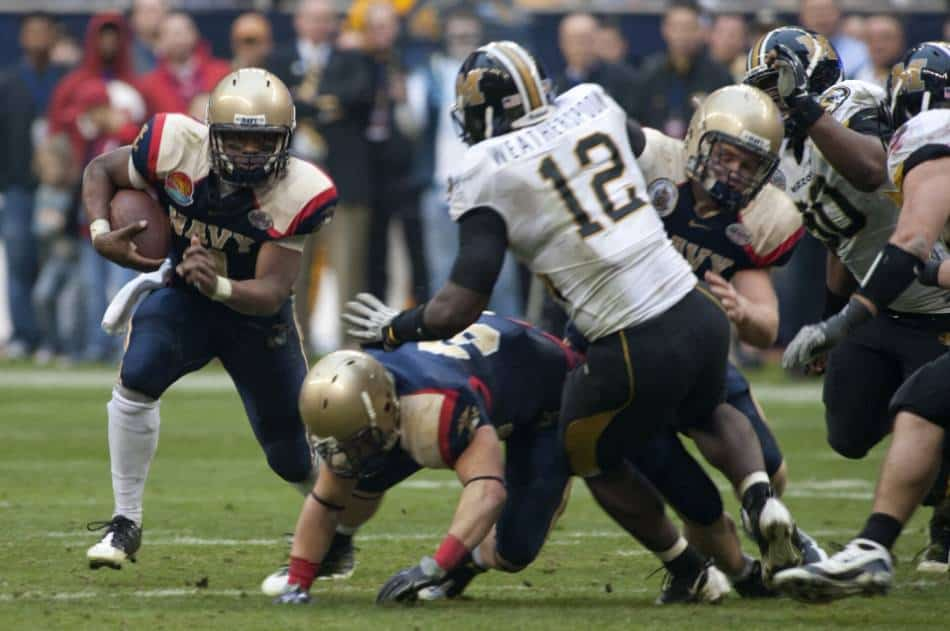A college football running back from Navy looks to run the ball outside.