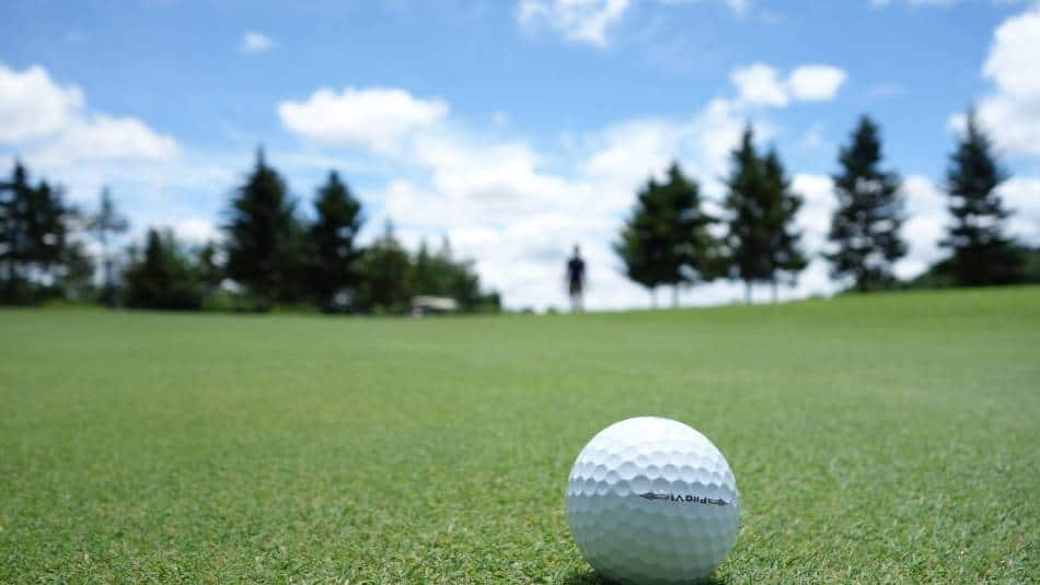 A golf ball and a golfer in the background.