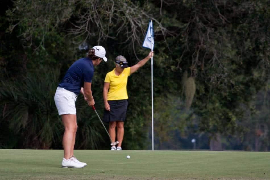 A female golfer in blue putts the ball.