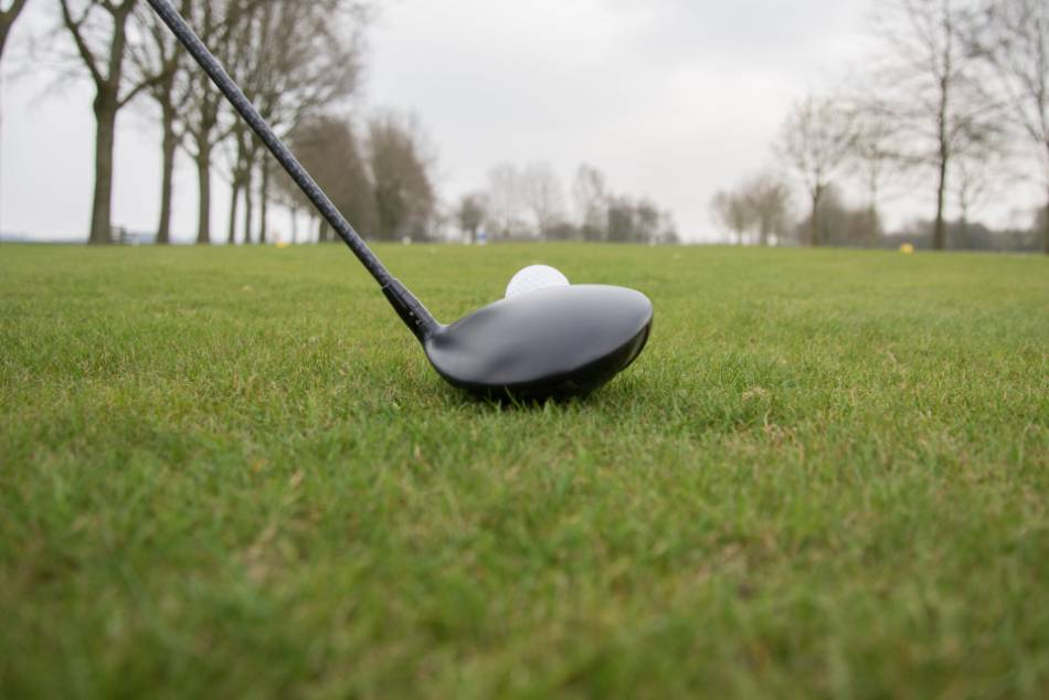 A golfer lines up his driver with the golf ball.