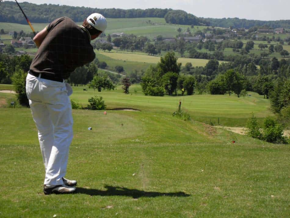 A golfer looks toward the hole after taking his swing.