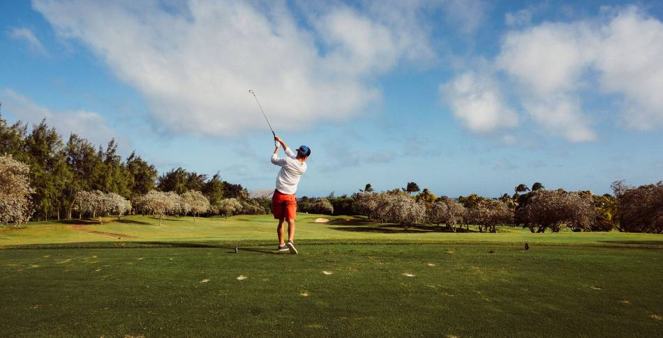 A golfer in orange shorts and a backward hat tees off.