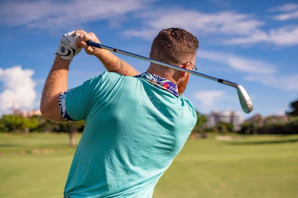 A golfer completes his follow through after swinging an iron.