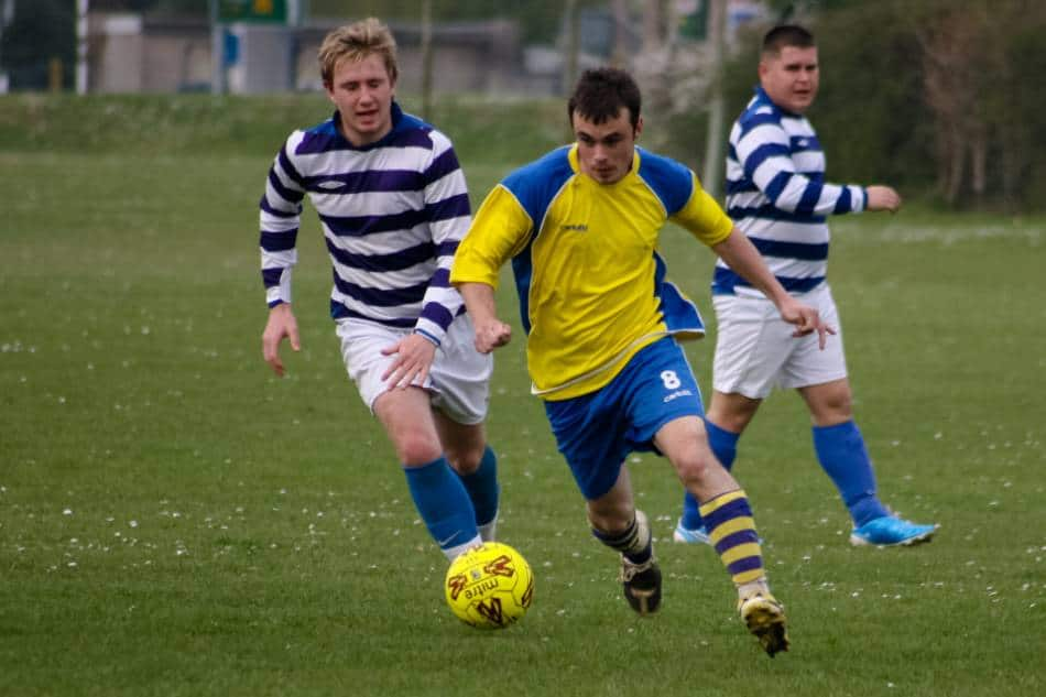 A soccer player in yellow and blue dribbles past a defender.