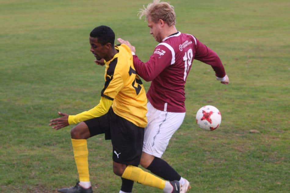 Two soccer players battle for possession of the ball.