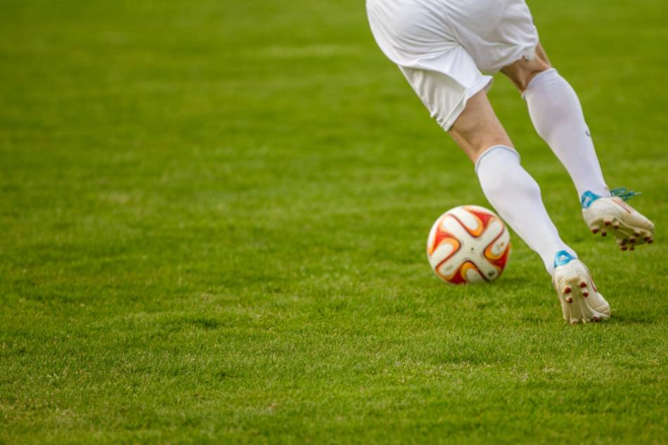 A soccer player dribbles the ball.