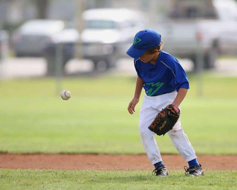 A Little League baseball player committing an error.