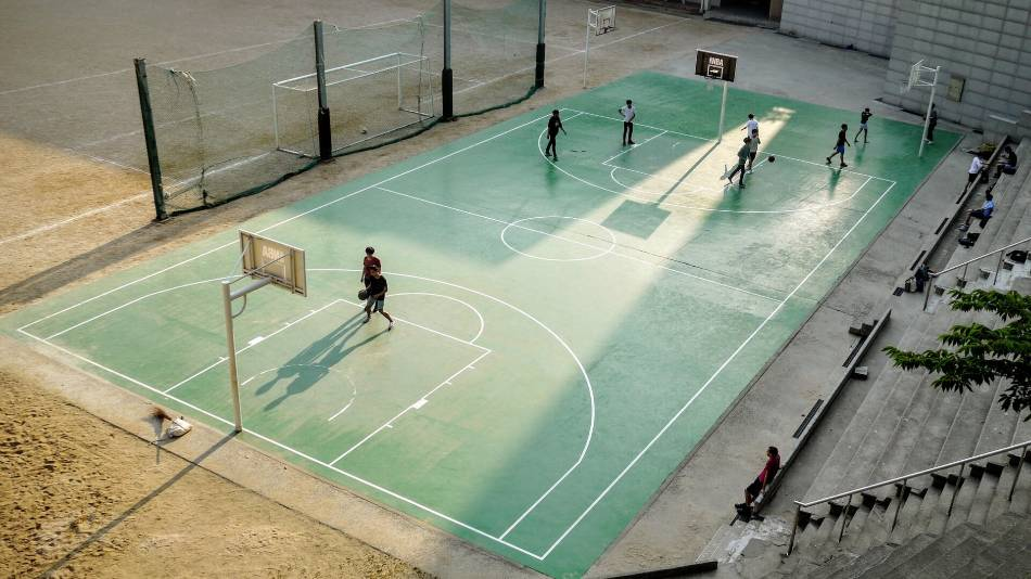 People playing basketball on an outdoor court.