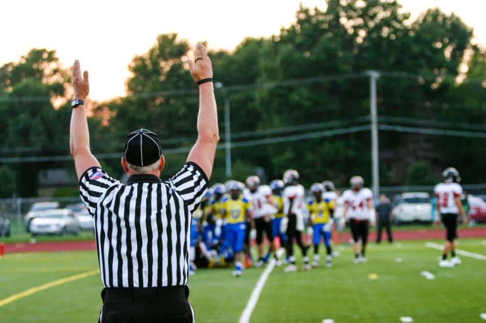 A high school football referee signals touchdown.