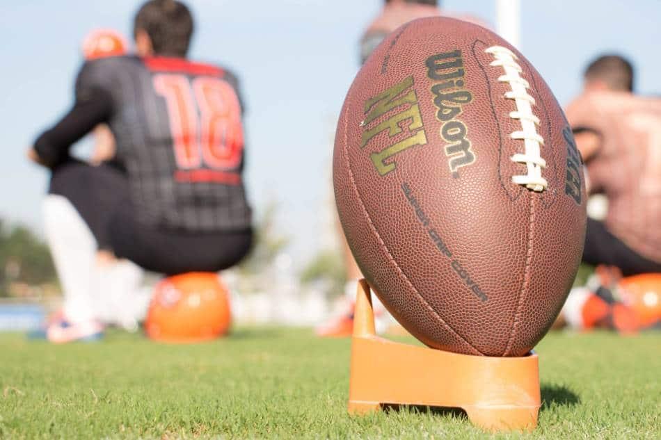 An NFL football sitting on a kicking tee.