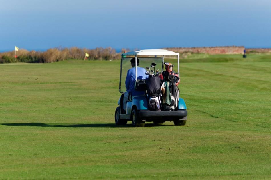 A golfer driving along the fairway in a cart.