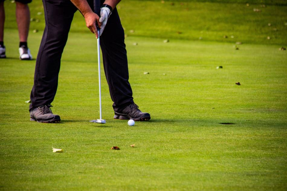 A golfer tries to putt his ball into the hole.