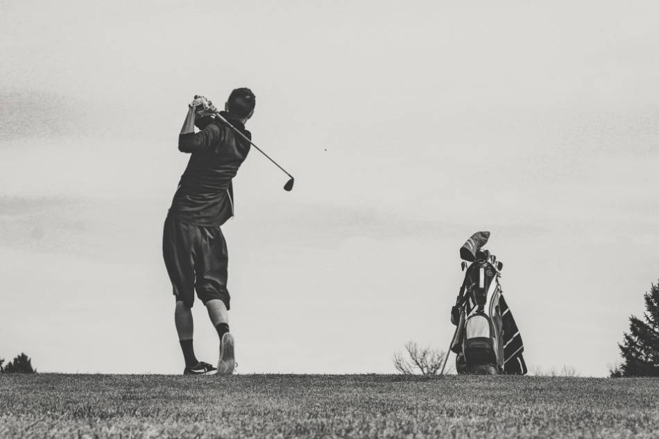 A golfer takes a swing with an iron.